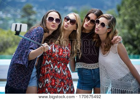 Beautiful women taking a selfie near swimming pool on a sunny day