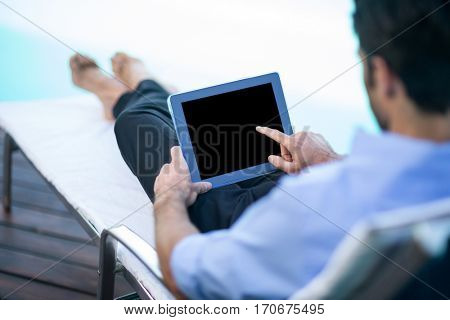 Man relaxing on sun lounger and using a digital tablet near the pool