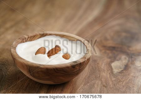 homemade yogurt with almonds in wood bowl on wooden table, shallow focus