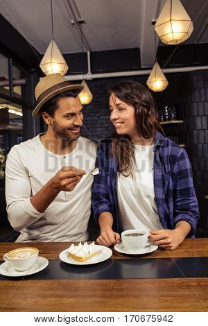 Man feeding woman with a piece of cake in a coffee shop