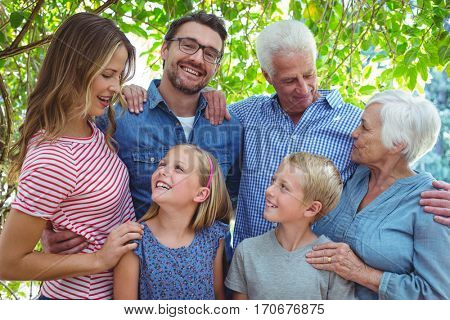 Happy multi generation family standing against tree