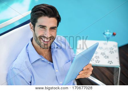 Portrait of smart man relaxing on sun lounger and using a digital tablet near pool