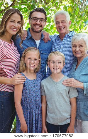 Portrait of smiling multi generation family standing against tree