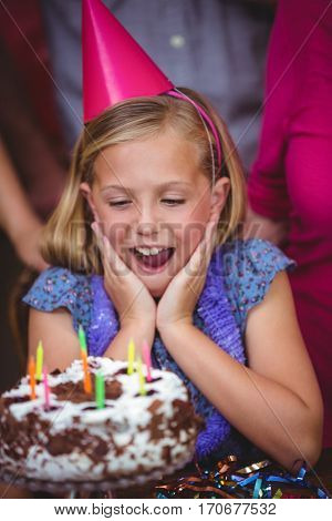 Shocked girl with birthday cake at home