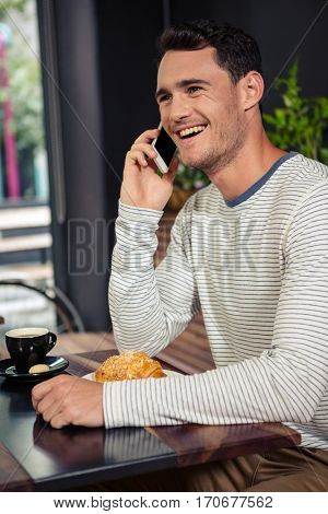 Happy man having a phone call in a coffee shop