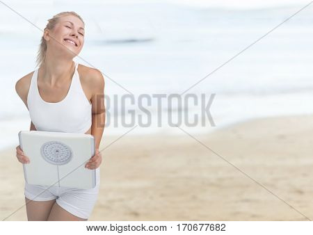 Smiling woman holding weighing scale on the beach