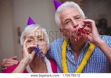 Close-up portrait of senior couple blowing party horn at home
