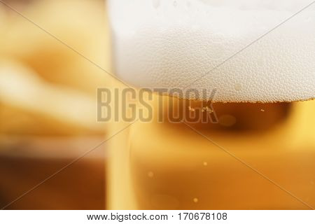 glass of lager beer closeup on wooden table, focus on beer