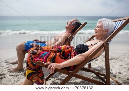 Happy senior couple relaxing on deckchairs at beach on a sunny day