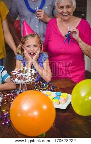 Portrait of shocked girl with family celebrating birthday at home