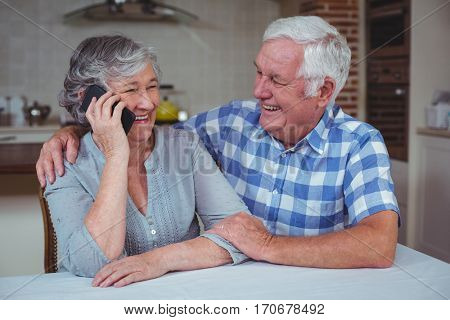 Happy senior woman talking on mobile phone while sitting with husband at table in kitchen