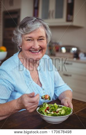 Portrait of happy senior woman having vegetable salad in kitchen
