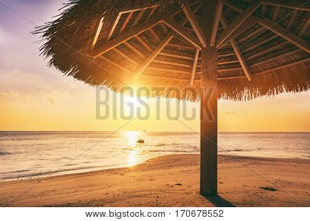 Sunset over tropical sandbank island with sunshade at sunset. Indian Ocean, Maldives. Blue sunny sky