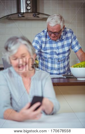 Senior woman with senior man in background standing at kitchen counter