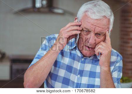 Worried senior man talking on mobile phone at home