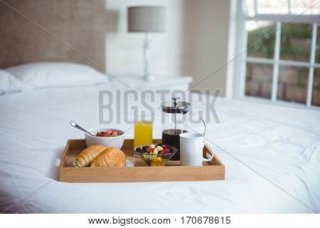Food and drink in serving tray on bed