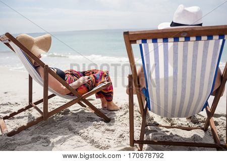 Rear view of happy senior couple relaxing on deckchairs at beach on a sunny day
