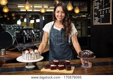 Smiling barista presenting plate with cakes at coffee shop