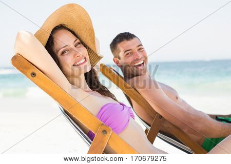 Couple relaxing on deck chair on the beach