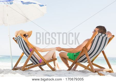 Happy couple sitting on deck chair on the beach