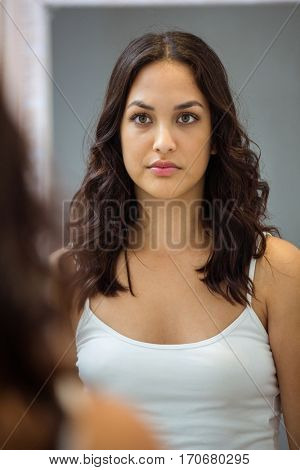 Beautiful young woman looking at herself in mirror at bathroom