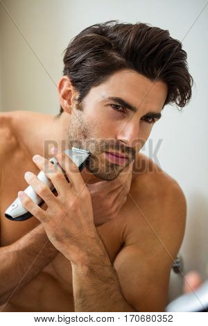 Reflection of young man shaving with trimmer in bathroom