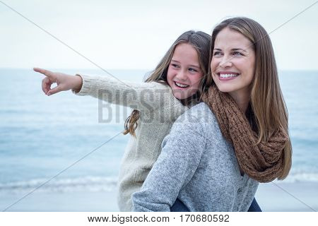Close-up of cheerful daughter pointing while mother carrying her at beach