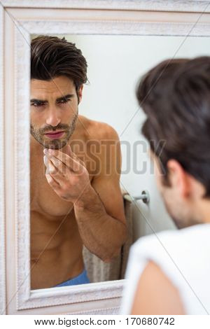 Man looking in mirror and checking his stubble in bathroom