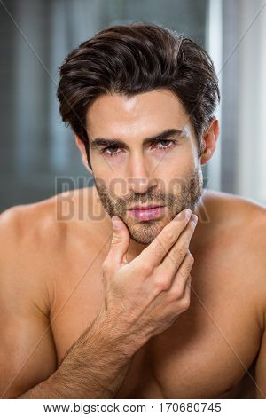 Portrait of young man checking his stubble in bathroom