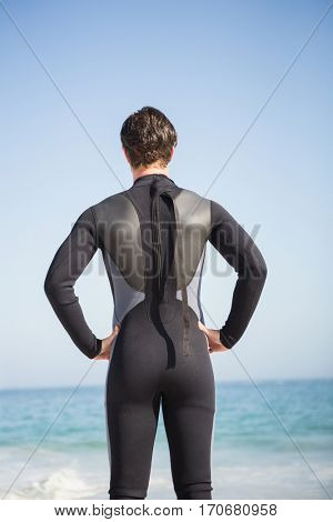 Man in wet suit posing on the beach