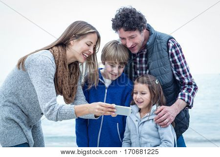 Happy family looking in cellphone while standing at beach