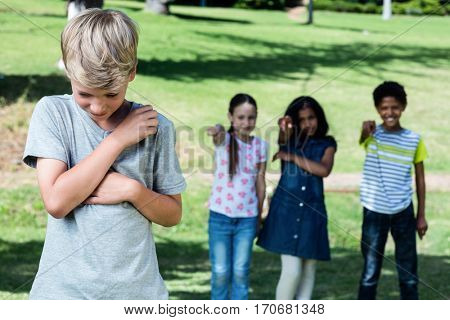 Friends teasing a boy in the park