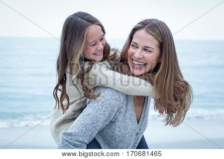Close-up of cheerful mother carrying daughter at sea shore