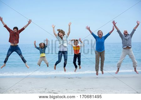 Full length of multi-generation family jumping at sea shore against blue sky