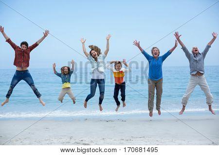 Full length of multi-generation family jumping at sea shore against blue sky