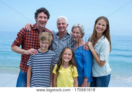Portrait of cheerful multi-generation family standing at sea shore against blue sky