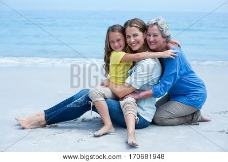 Portrait of cheerful multi-generation family relaxing at sea shore