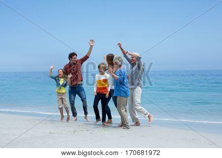 Cheerful multi-generation family dancing at sea shore against blue sky