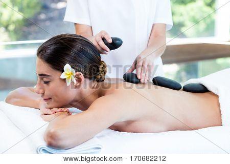 Beautiful woman receiving stone massage at spa