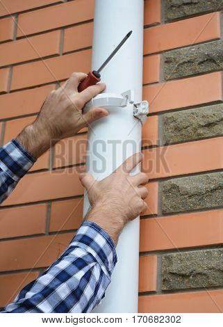 Contractor installing and repair pvc rain gutter system pipeline. Guttering Plastic Guttering & Drainage by Handyman hands.