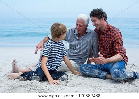 Multi-generation family smiling while resting at sea shore