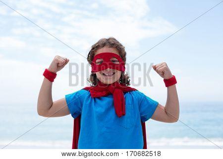 Portrait of happy boy in superhero costume flexing muscles at sea shore