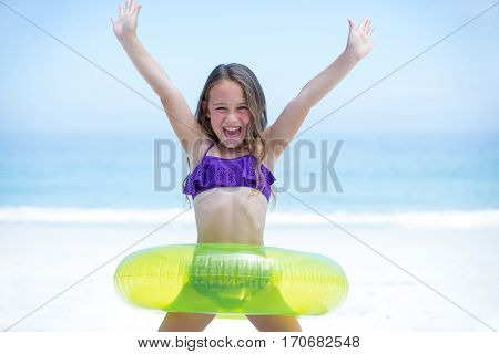 Portrait of girl with inflatable ring enjoying at sea shore against blue sky