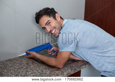 Portrait of smiling man using pest control injection while standing at home