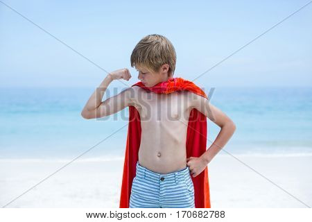 Shirtless boy in superhero costume flexing muscles at beach