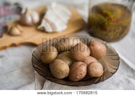 Potatoes Baked In Their Jackets. Potatoes In Their Skins, Bacon, Garlic And Pickles On The Table.