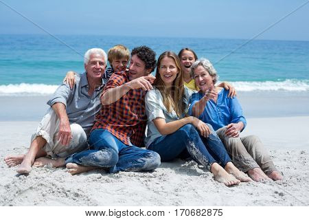 Cheerful multi-generation family relaxing at sea shore on sunny day