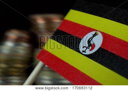 Uganda Flag Waving With Stack Of Money Coins Macro