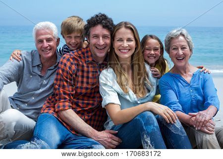 Portrait of cheerful multi-generation family relaxing at beach
