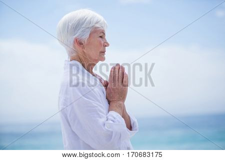 Side view of senior woman with hands clasped at beach against sky